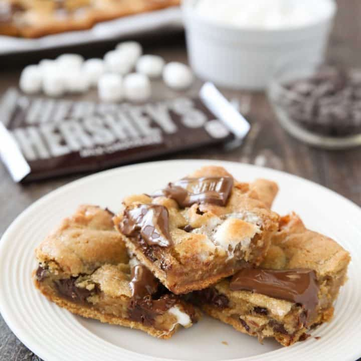 S'mores Cookie Bars are layered with graham crackers, cookie dough with marshmallows, and topped with chocolate bar pieces. It's an ooey gooey melty chocolate s'mores treat!