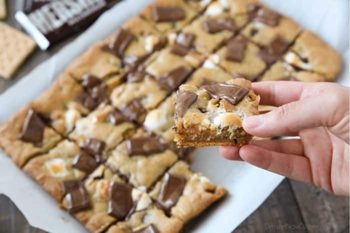 Warm and gooey s'mores cookie bars with graham crackers on bottom, marshmallows inside, and chocolate pieces on top.