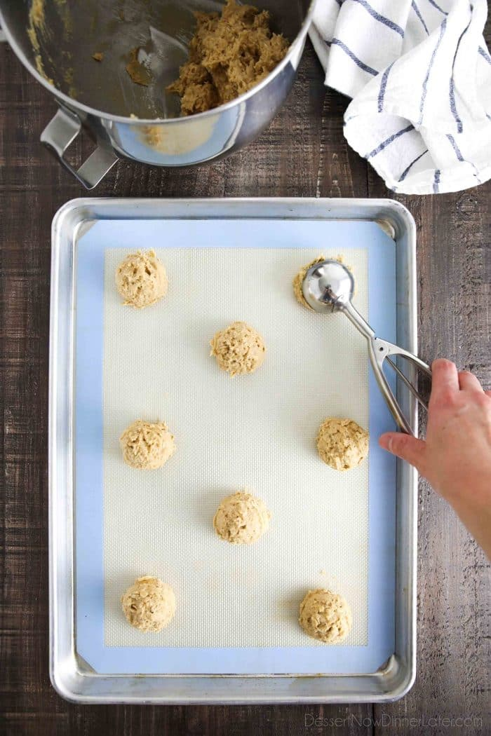 Scooping peanut butter oatmeal cookie dough onto a cookie sheet.