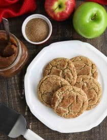Crinkle topped apple butter cookies on plate with apple butter, cinnamon sugar, and fresh apples nearby.
