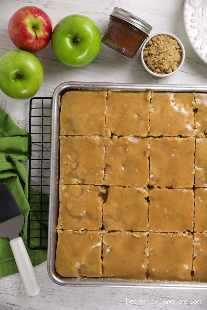 Glazed apple sheet cake in a pan cut into slices.