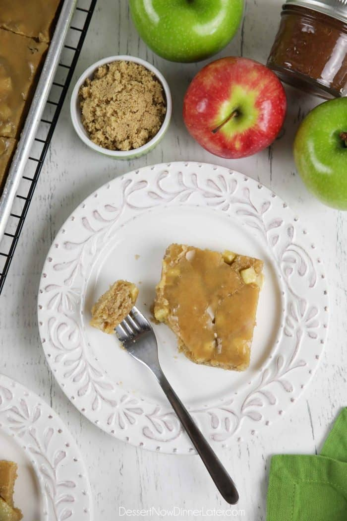 Slice of glazed apple sheet cake on a plate with a fork full of cake.