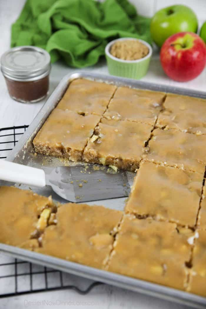 Apple sheet cake with brown sugar glaze in pan with a couple pieces missing.