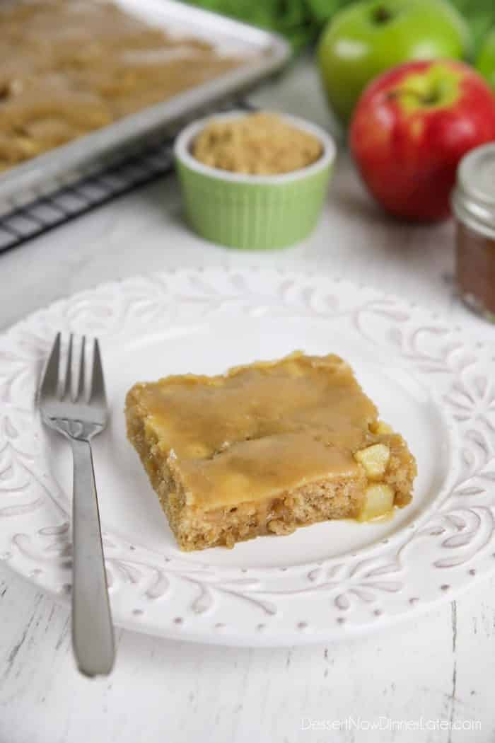 Slice of brown sugar glazed apple sheet cake on a plate with a fork.