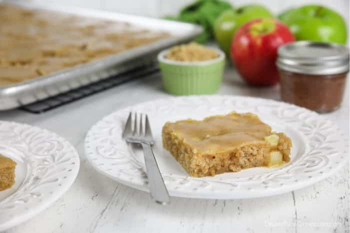 Slice of apple sheet cake on plate with fork.