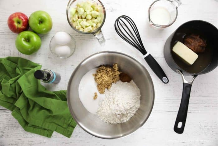 Apple sheet cake ingredients: flour, baking soda, salt, sugar, brown sugar, cinnamon, butter, apple butter, water, buttermilk, eggs, vanilla, and diced apple.