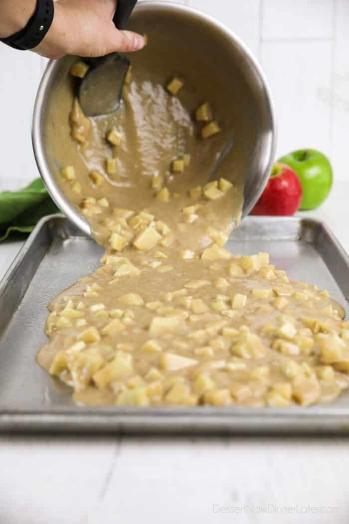 Apple cake batter being poured into sheet pan.