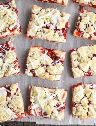 Squares of glazed cherry pie bars on parchment paper and a cooling rack.