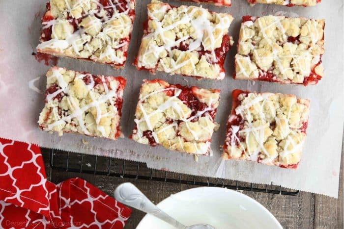 Cherry pie bars on top of parchment paper and a cooling rack.