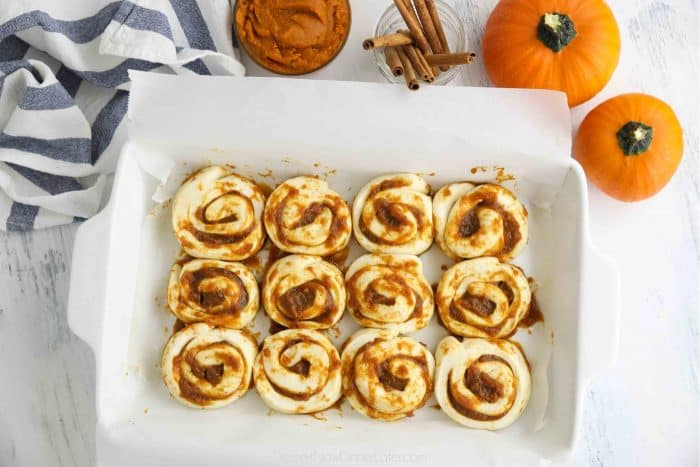 Pumpkin pie cinnamon rolls placed in baking pan fitted with parchment paper ready to bake.