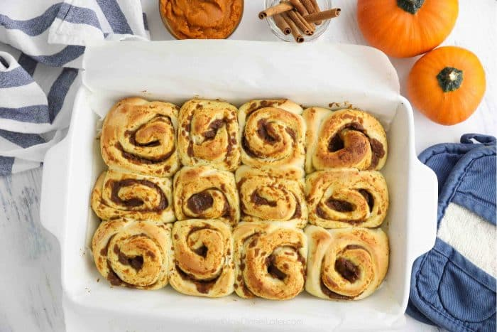 Pumpkin cinnamon rolls in pan after being baked.