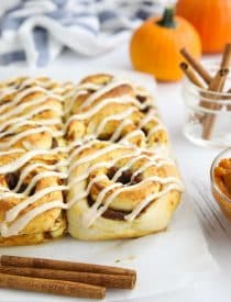 Pumpkin Pie Cinnamon Rolls drizzled with cream cheese frosting sitting on parchment paper.