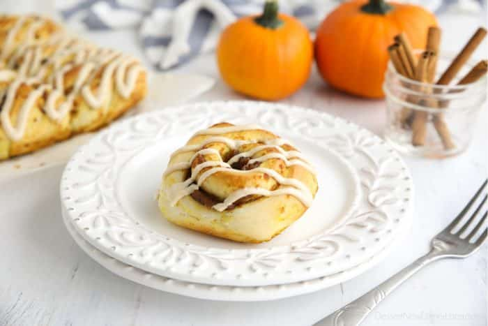 A Pumpkin Pie Cinnamon Roll on a plate with decorative pumpkins and cinnamon sticks in the background.