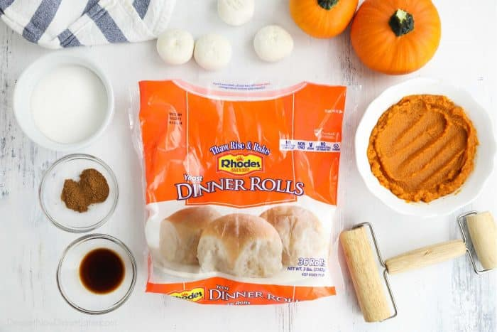 A bag of Rhodes Yeast Dinner Rolls surrounded by other ingredients in bowls, with a mini rolling pin on the side.