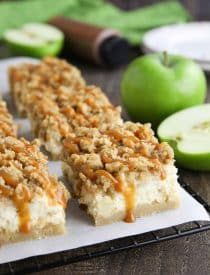 Caramel Apple Cheesecake Bars on a parchment lined wire cooling rack with caramel dripping down the sides.