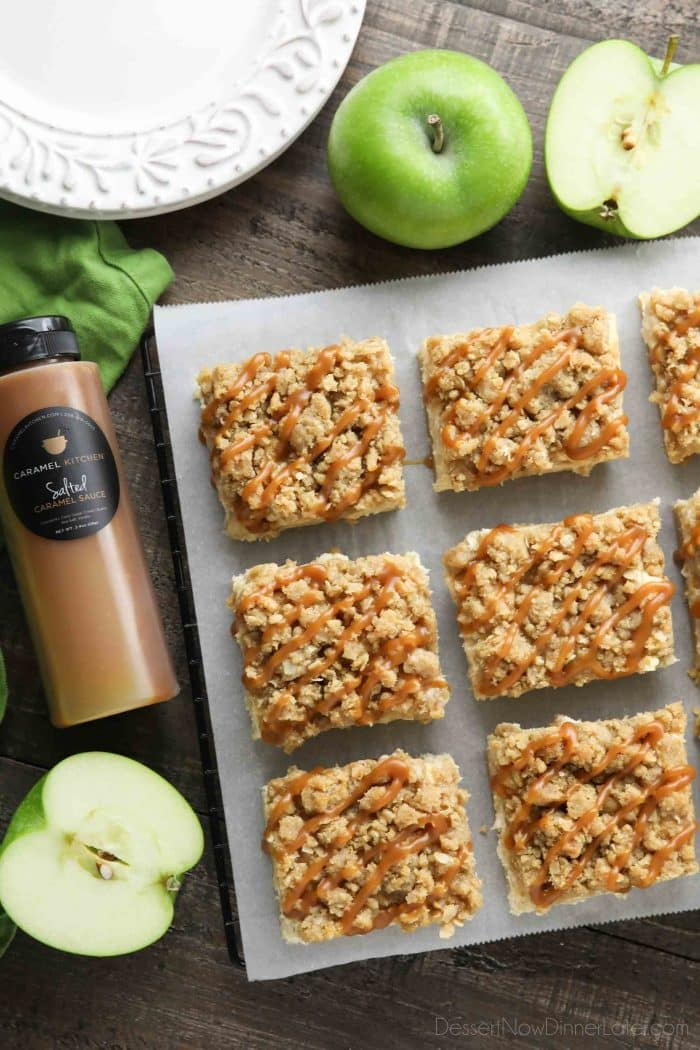 Squares of caramel apple cheesecake bars on parchment paper surrounded by Granny Smith apples and a bottle of salted caramel.