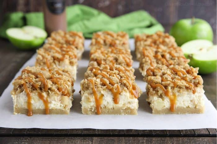 Caramel dripping down the sides of sliced apple cheesecake bars.