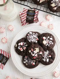 Plate of chocolate peppermint cookies surrounded by round peppermint candies and square peppermint bark chocolates.