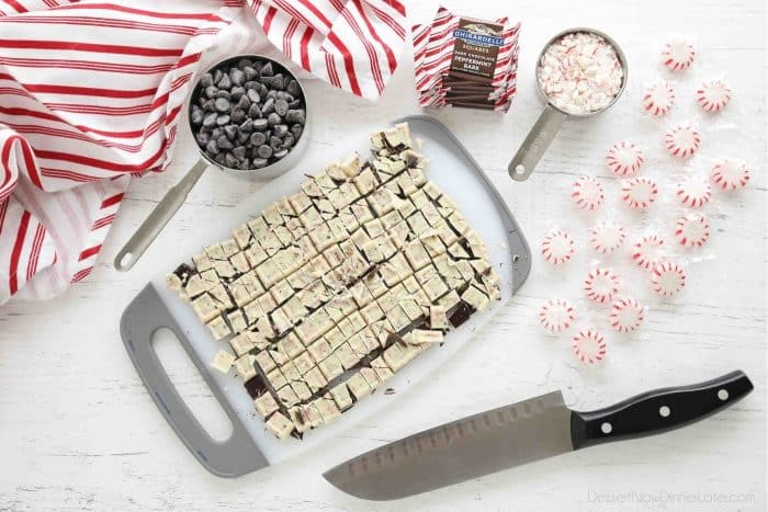 Peppermint bark squares chopped on a cutting board with a chef's knife on the side. Measuring cups full of chocolate chips and crushed peppermint candies.