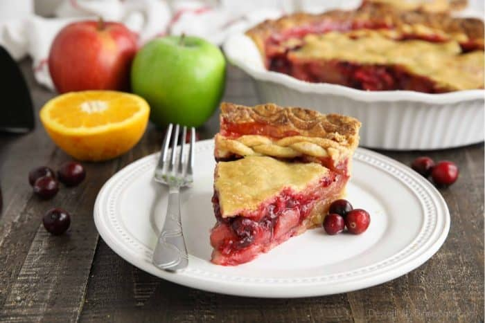 Slice of cranberry apple pie on plate with fork.