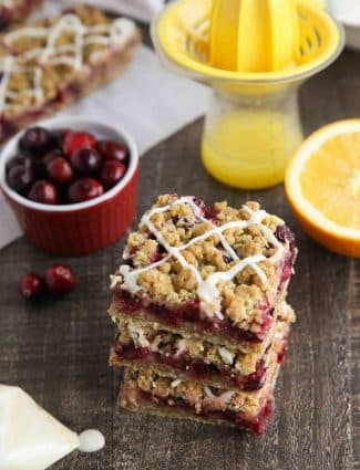 Cranberry Crumble Bars stacked with glaze drizzled on top.