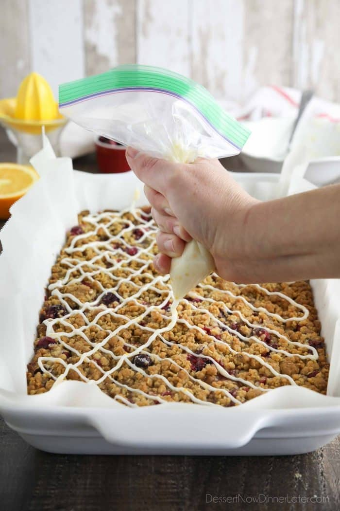 Squeezing orange glaze over baked cranberry bars.