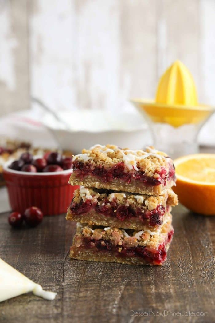 Side view of cranberry crumble bars stacked on top of each other.
