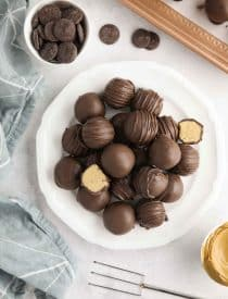 Easy Peanut Butter Balls stacked on a plate. Some drizzled, some plain, and two halves showing the peanut butter interior.