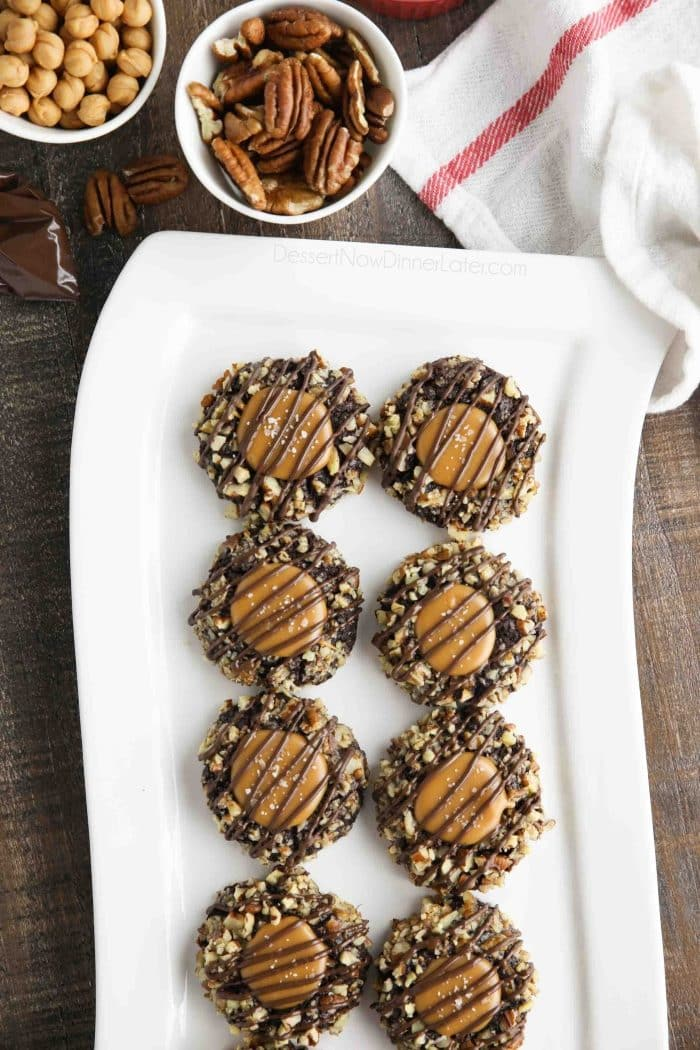 Long white plate of turtle thumbprint cookies with pecans and caramel bits nearby.