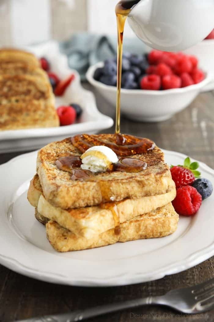 Classic French Toast stacked on a plate with syrup being poured over the top.