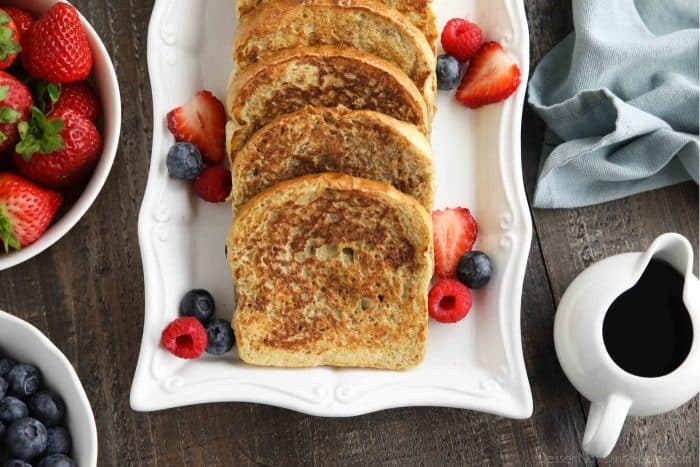Plate of cinnamon french toast with fruit and syrup on the side.