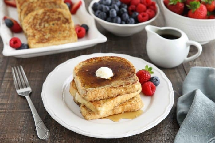 Stacked French toast with butter and syrup.