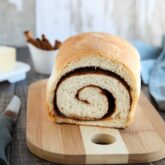 Loaf of cinnamon bread on a cutting board with a slice removed to show the cinnamon swirl on the inside..