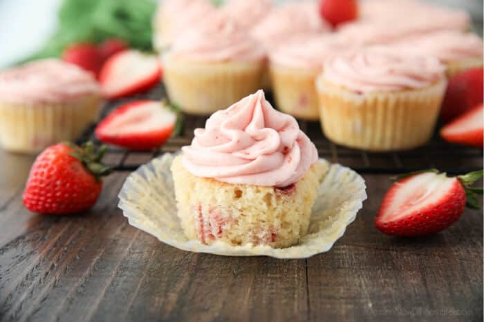Fresh strawberry cupcake in wrapper with strawberry frosting on top.