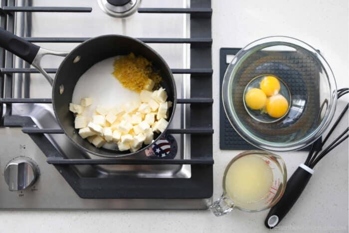 How to make lemon curd. Five ingredients: granulated sugar, lemon zest, lemon juice, butter, and egg yolks.