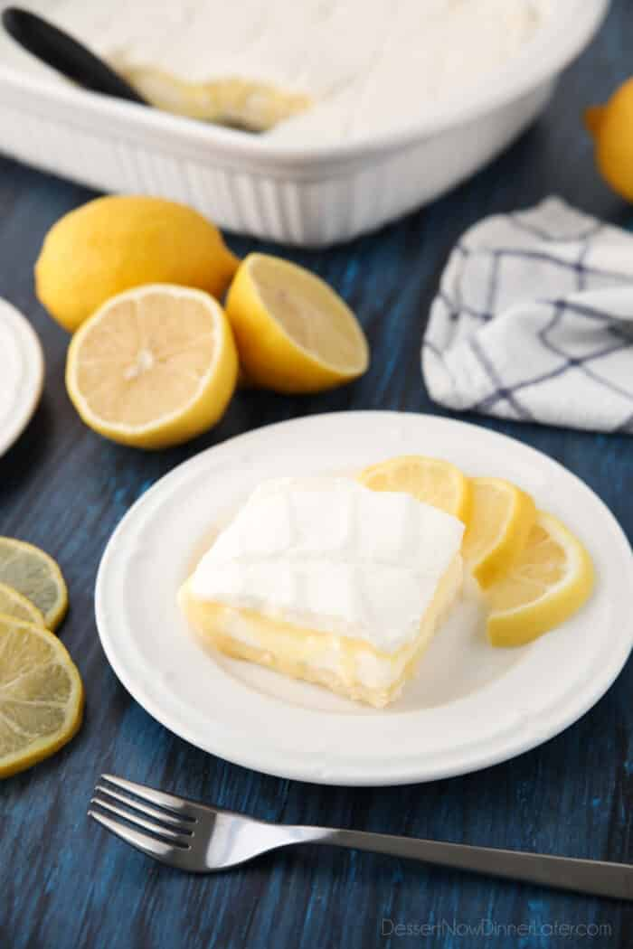 Lemon curd dessert square on plate made with a shortbread crust, sweetened cream cheese, lemon curd, and whipped cream.