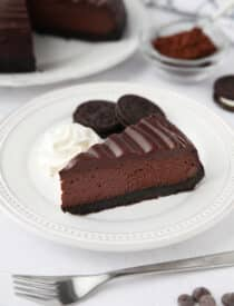 A slice of Triple Chocolate Cheesecake on a plate with Oreos and whipped cream on the side.