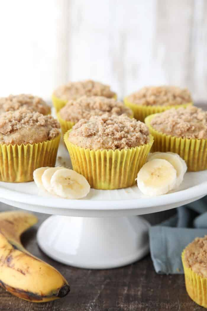 Cake plate with banana crumb muffins and slices of bananas.