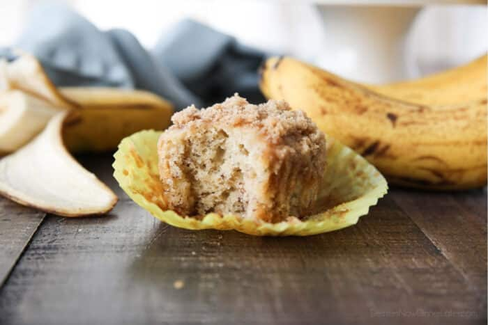 Side view of a banana crumb muffin with a bite taken out.