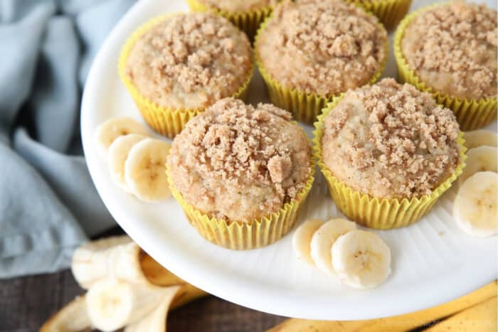 White cake plate with banana muffins in yellow wrappers with crumb streusel on top and slices of banana on the sides.