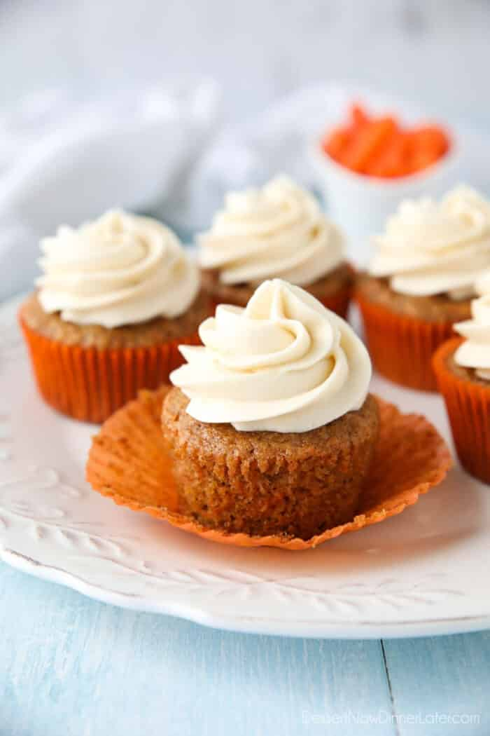 Carrot Cake Cupcakes on a plate. Focus is on a cupcake with the paper liner pulled down on the sides to show velvety texture of cake.