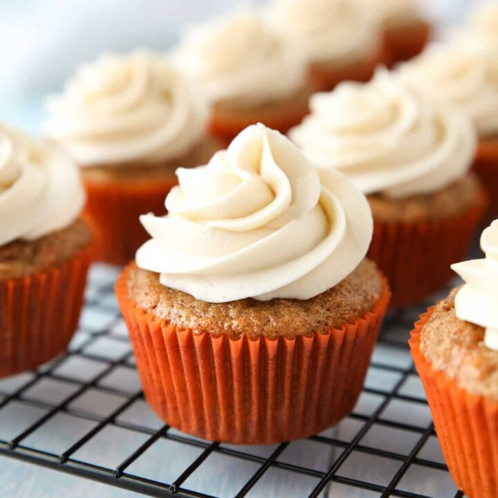 Cooling rack with cream cheese frosted carrot cake cupcakes.