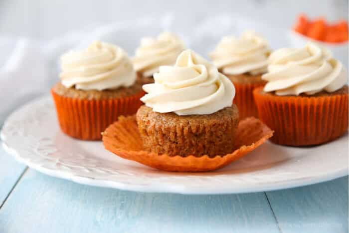 Carrot Cake Cupcakes on a plate. Focus is on a cupcake with the paper liner pulled down on the sides.