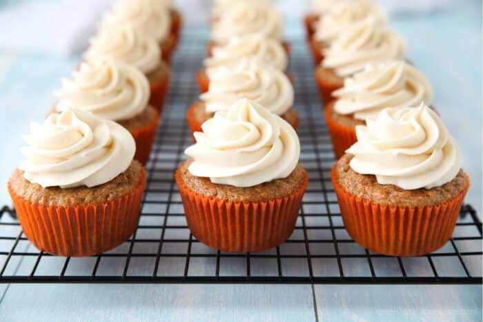 Cream cheese frosting piped on top of carrot cake cupcakes on a cooling rack.