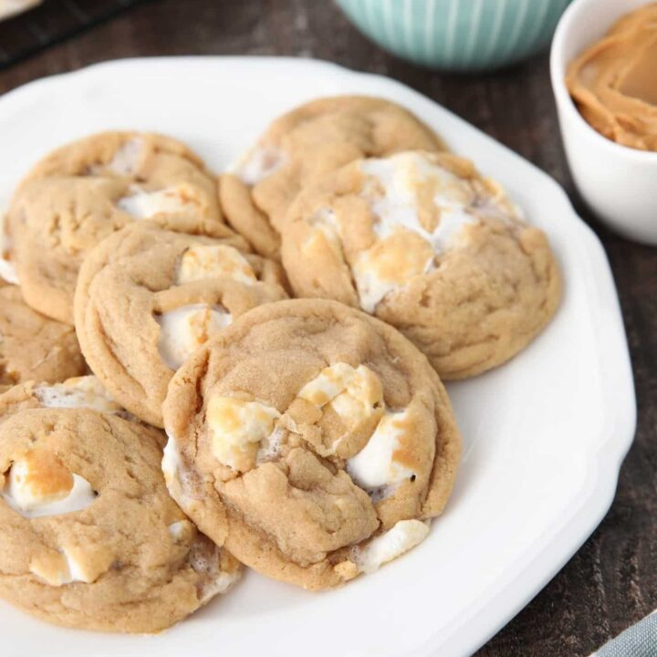 Fluffernutter cookies on a plate with bowls of mini marshmallows and peanut butter in the background.