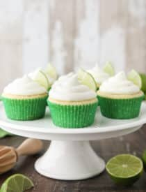 Key Lime Cupcakes sitting on a cake stand with lime wedges in frosting.