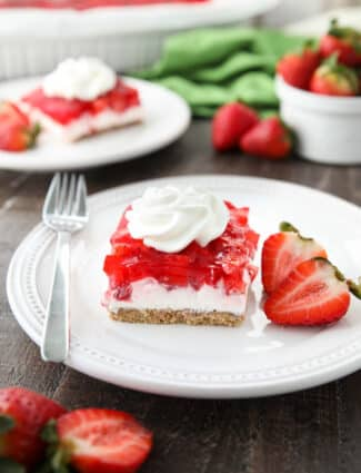 A square of strawberry delight on a plate. (A layered dessert with a graham cracker crust, no bake cheesecake filling, and a layer of fresh strawberries and jello with a swirl of whipped cream on top.)