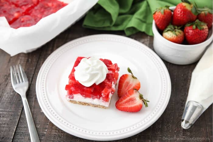 A piece of strawberry delight on a plate with a halved strawberry on the side.