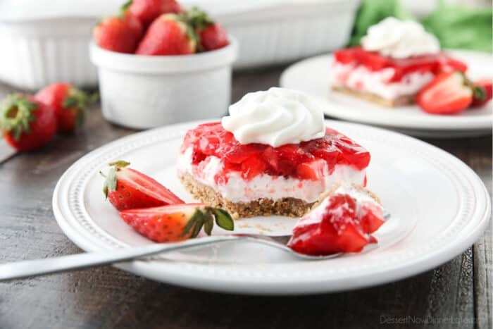A square of strawberry delight on a plate. A layered dessert with a graham cracker crust, no bake cheesecake filling, and a layer of fresh strawberries and jello with a swirl of whipped cream on top.