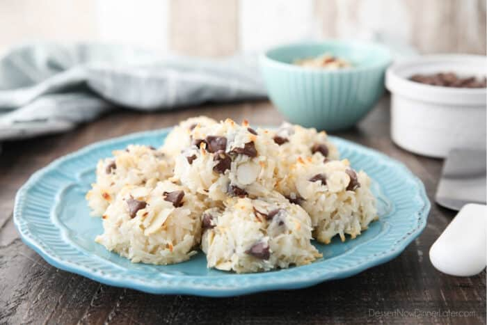 Side view of a plate of coconut macaroons with almonds and chocolate chips.